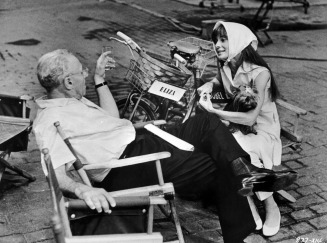 circa 1964: American film director George Cukor (1899-1983) and Belgian-born actor Audrey Hepburn (1929-1993) sit in director's chairs and talk, on the set of the film, 'My Fair Lady.' (Photo by Hulton Archive/Getty Images)
