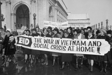 15 Jan 1968, Washington, DC, USA --- A group of women belonging to the Jeanette Rankin Brigade march in protest of the Vietnam War. Jeanette Rankin, the first female congress member, stands holding the banner at center (wearing eyeglasses). --- Image by © Bettmann/CORBIS